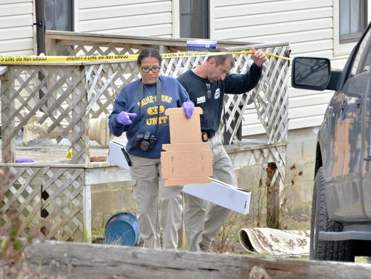 Officers investigate the scene of a shooting near Iuka,
