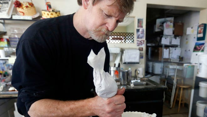 In 2014 file photo, Masterpiece Cakeshop owner Jack Phillips decorates a cake inside his store in Lakewood, Colo. Monday, a divided Supreme Court absolved him of discrimination for refusing to create a custom wedding cake for a same-sex couple.
