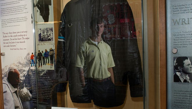 Collin Bryant, a senior at Pope John Paul II High School in Hendersonville, Tenn., is reflected Oct. 4, in the display case for a ski jacket once worn by Pope John Paul II, who will be canonized a saint by Pope Francis.