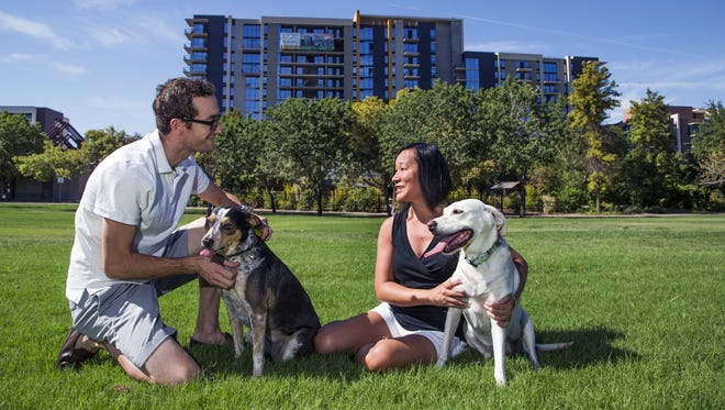 Karen Wang and her partner, Logan Stephenson, play with their dogs Sophie (right) and Olivia at Margaret T. Hance Park in Phoenix on July 21, 2016. Wang has purchased a condo in the Portland on the Park project under construction.