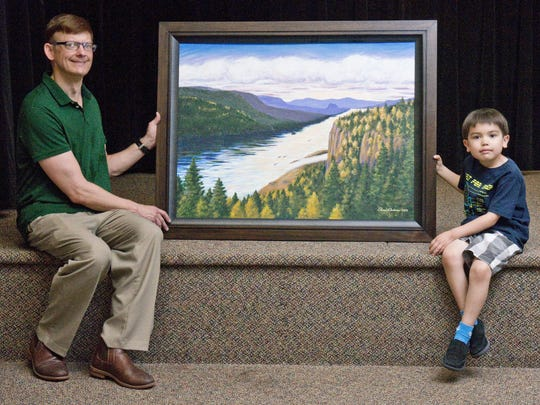 Ross Anderson with son Gavin, 7, and Anderson's painting of the Columbia River Gorge, which divides Washington and Oregon. Anderson said the scene was inspired by the journey of the explorers Lewis and Clark.