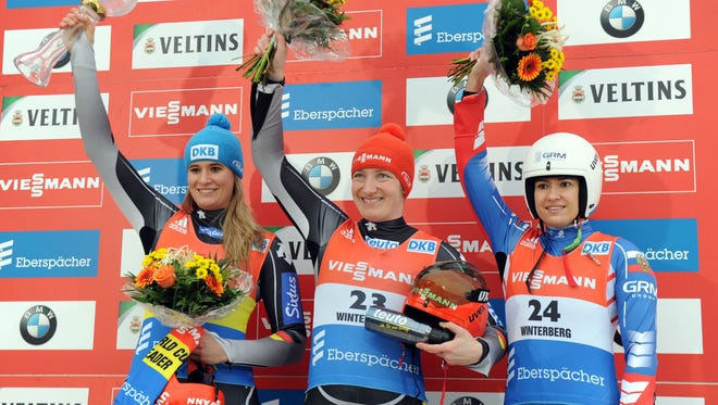 Natalie Geisenberger (second place), Tatjana Hufner (first place) and Tatiana Ivanova (third place) acknowledge the crowd from the podium after the women's single luge World Cup race in Winterberg, Germany, Saturday. Geisenberger won the season's World Cup championship.