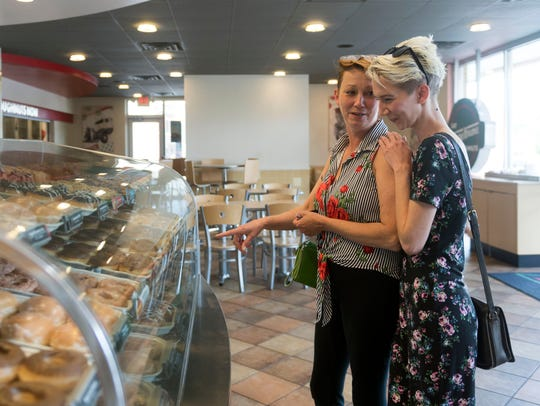 Shelley and Emilie Malcom pick out a dozen doughnuts at the Krispy Kreme on Kingston Pike on Monday. The two don't count calories , but chain restaurants are being required to display caloric content information on their menus.