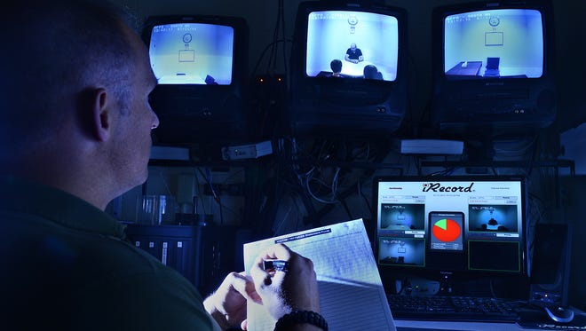 A photo illustration of the interrogation rooms monitoring station at the Great Falls Police Department.