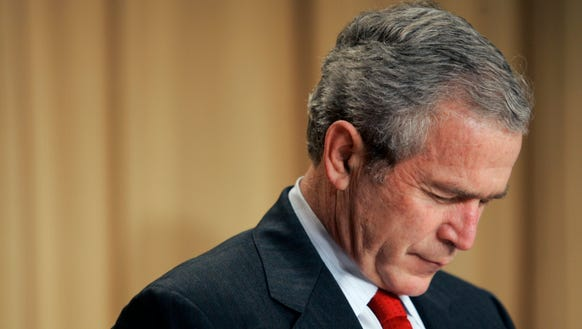 President George W. Bush bows his head during the invocations