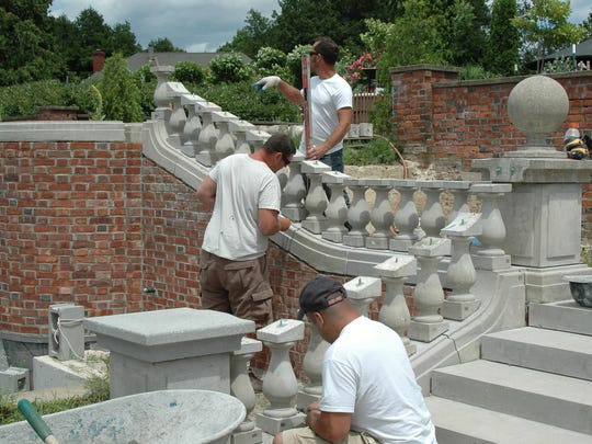 Masons work to reconstruct balusters around the lower garden and lily pool.