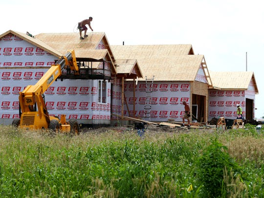 Workers build new homes in the North Gate residential community in Ankeny in 2014.
