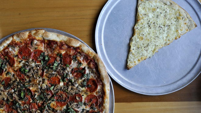 Pepperoni and mushroom pie with fresh basil and a slice of white pizza.