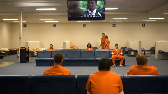 Inmates watch television in one of the newer intake areas at the Larimer County Detention Center in this 2014 file photo.