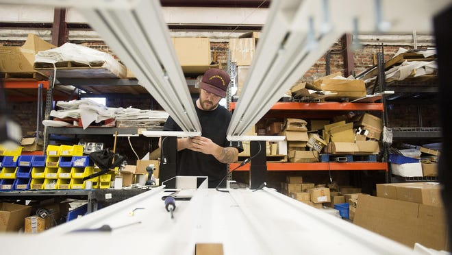 Andrew Kurtz builds a desk for SBFI in a warehouse on Lyman Street. Tom Finger, owner of SBFI, has been based in the River Arts District since the '80s and builds custom desks for large investment banks around the world.