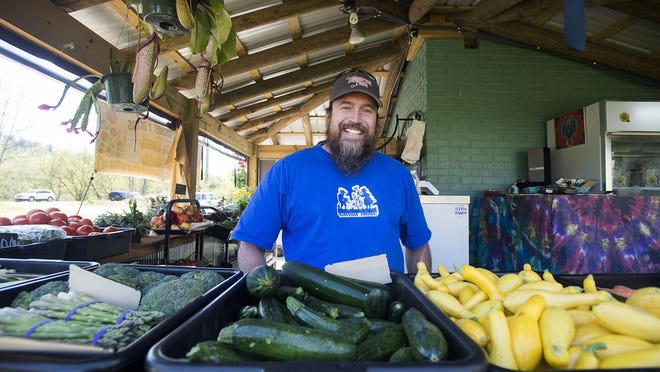 Kendall Huntley of Whispersholler Farms stands where he sells a variety of fruits, vegetables, plants, and more at the Asheville Food Park Thursday April 14, 2016.
