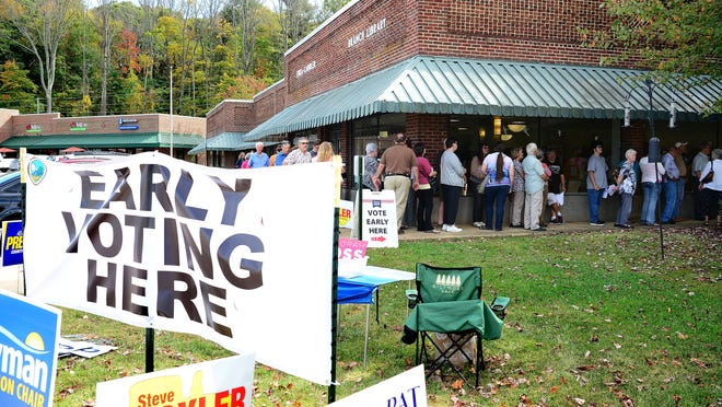 The line at the Enka-Candler Library wraps around the corner of the building on the first day of early voting in 2016 as people wait to cast their ballots.
