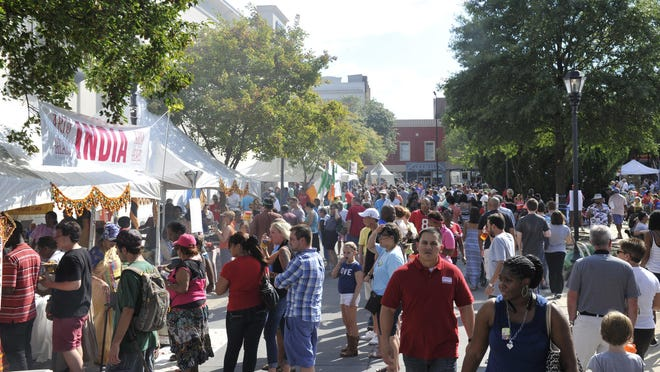 People walk by food tents at the Augusta Common during the 2014 Arts in the Heart of Augusta Festival.
