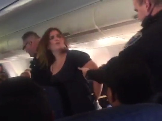 "A woman was escorted off of an American Airlines flight the evening of Sept. 14, 2015, after being ""unruly"" and hitting a flight attendant and another passenger. The woman was not immediately identified."