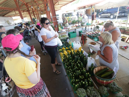 West Allis Farmers Market customers gather at the stall of Cindy's Greenhouse and Fresh Vegetables of East Troy as owner Cindy Chapman (second from right) and her daughter Jessie Stocchetti bag produce.