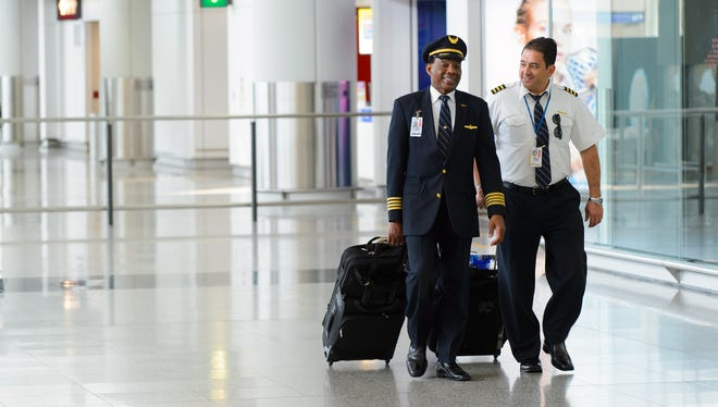 United Airlines pilots walk through an airport in Hong Kong.