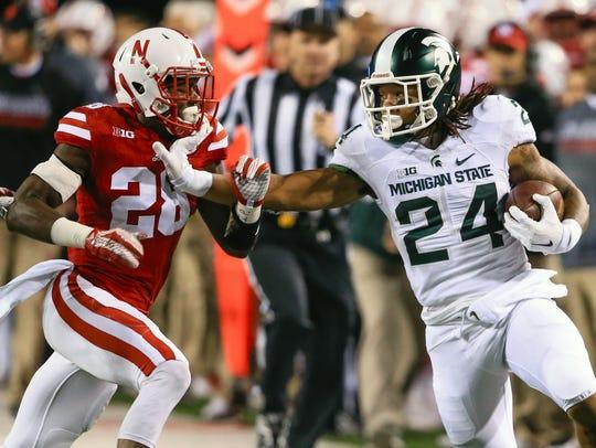 Michigan State running back Gerald Holmes stiff-arms