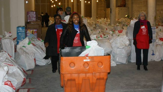 Volunteers at the D.C. Salvation Army Angel Tree warehouse move bag of gifts for children in need.