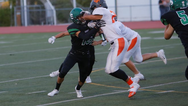 Farmington's Juan Medrano tries to stop Aztec's Alex Parra on Sept. 14, at Hutchison Stadium. The Scorpions will take on Kirtland Central on Friday.