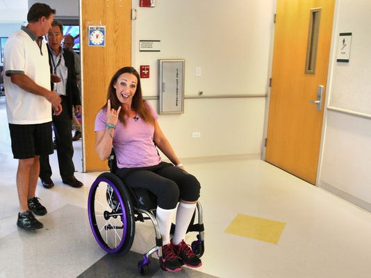 FILE - In this Aug. 14, 2014, file photo, AmyVanDyken-Rouen gestures as she leaves Craig Hospital with her husband, Tom Rouen, left, in Englewood, Colo. Van Dyken-Rouen was left paralyzed just below the waist in an all-terrain vehicle crash. Her occasional updates on social media have been upbeat and filled mostly with good news. She is excited to face the challenge of learning how to live without use of her legs. Her enthusiasm is not an act. (AP Photo/Brennan Linsley, File)