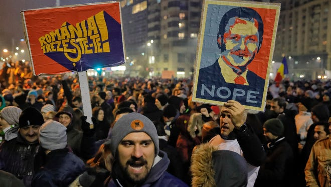 People hold posters depicting the leader of the ruling Social Democratic party Liviu Dragnea, the other reading 'Romania-Wake Up,' during a protest in Bucharest on Feb. 1.