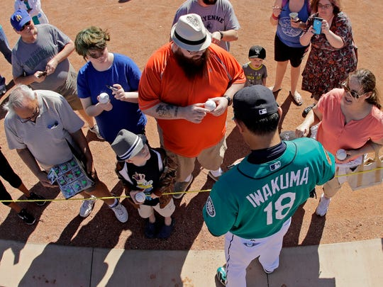 Pitcher Hisashi Iwakuma signs autographs for fans last week at the Mariners' spring training complex in Peoria, Ariz.