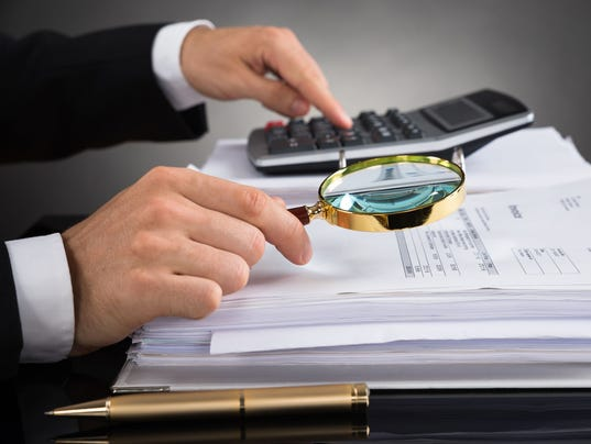 Businessperson Checking Invoice With Magnifying Glass