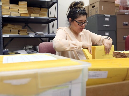 In this 2016 file photo, temporary election clerk Miranda Sanchez prepares voting packets at the Nueces County Courthouse.