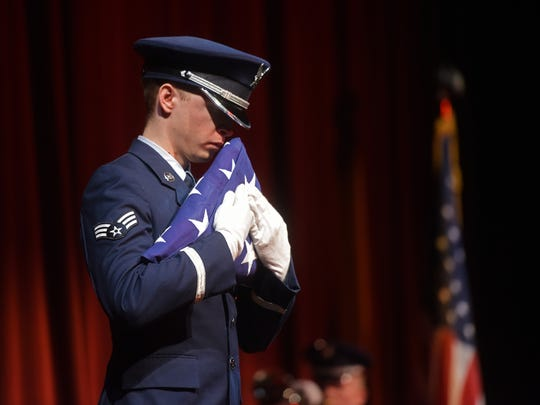 A member an Air Force honor guard holds an American flag during the playing of taps at the service for Byrne.