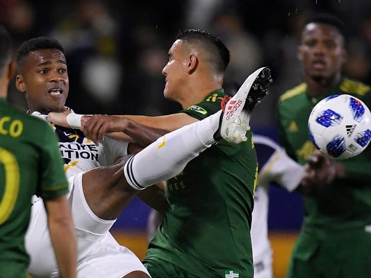 Los Angeles Galaxy forward Ola Kamara, left, tries to kick the ball as he is shoved away by Portland Timbers midfielder David Guzman during the first half of a Major League Soccer game, Sunday, March 4, 2018, in Carson, Calif. (AP Photo/Mark J. Terrill)