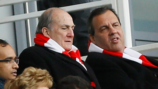 New Jersey Gov. Chris Christie, top right, wearing an Arsenal scarf, sits with Rutgers University President Robert Barchi, left, in the stands during the English Premier League soccer match between Arsenal and Aston Villa at the Emirates stadium in London, Sunday, Feb. 1, 2015.