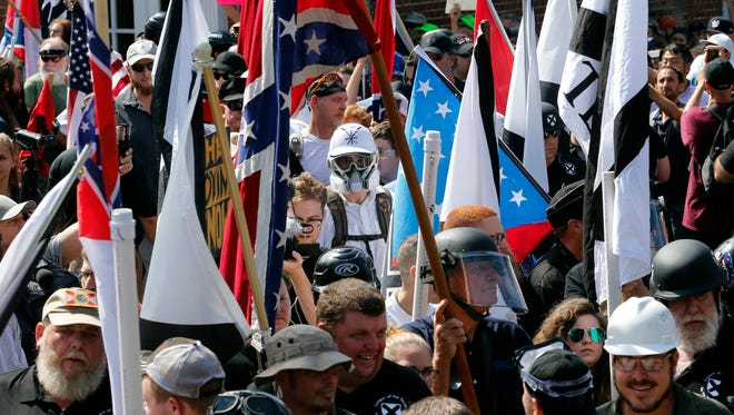 White nationalist demonstrators walk into the entrance of Lee Park surrounded by counter demonstrators in Charlottesville, Va.