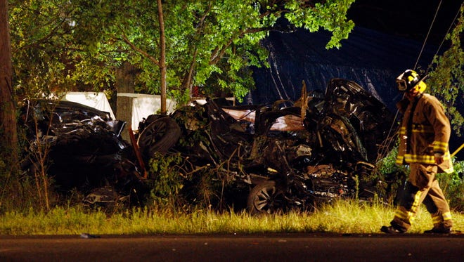 A firefighter works at the scene of an accident with multiple fatalities Aug. 11, 2014, in in League City, Texas. Authorities say six people have been killed, including a family of four, when an SUV speeding from police struck another vehicle southeast of Houston.