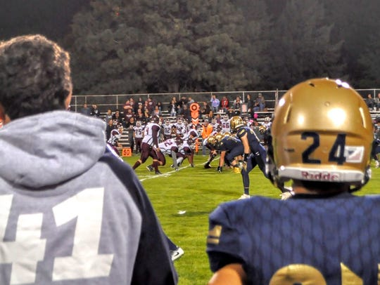 Players look on from the sidelines as Ruidoso play