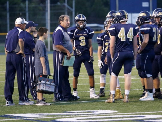 Notre Dame head coach Mike D'Aloisio talks to his players during a timeout Friday during the Crusaders' 26-0 win over Thomas A. Edison.