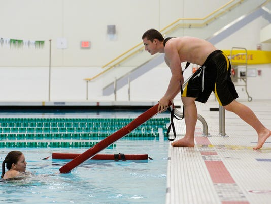 York Suburban freshman Aiden Fryar, right, practices helping York College freshman Samantha Hay to safety using a buoy during an American Red Cross lifeguard certification course on Friday, May 1, 2015, at York College's Grumbacher Sport and Fitness Center. The certification courses will continue through the weekend, and successful completion will result in a two-year certification. Chris Dunn Ñ Daily Record/Sunday News