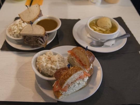 The menu at Shapiro's New York Style Delicatessen in Red Bank includes (clockwise from front) homemade chicken salad on a pretzel croisant, brisket on rye with brown gravy and macaroni salad, and matzo ball soup.