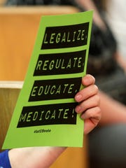 An attendee holds a sign in favor of legalizing marjiuana at a Brown County board meeting at city hall on Wednesday, July 18, 2018 in Green Bay, Wis. Members of the public spoke to the county board Wednesday as it weighed whether or not election ballots this fall will include non-binding questions about the legality of marijuana. 
