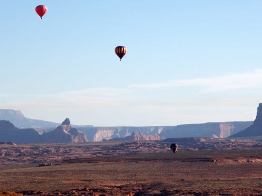 Hot air balloons float throughout he skies while Tower Butte and the cliffs of Glen Canyon National Recreation Area stand in the background as they drift east on the early morning winds Sunday, Nov. 3, 2013 in Page, AZ..