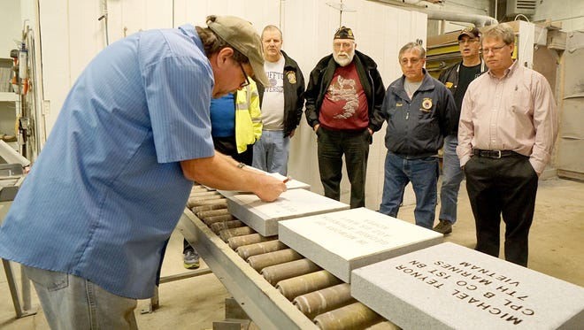 Ken Ewing, of Longstreth Memorials, show the process for creating the pavers for Crawford County Veterans Hall of Fame monument to area veterans.