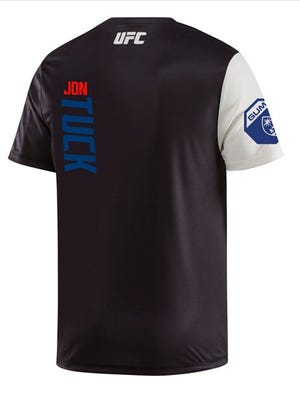 The back of Jon Tuck's UFC Fight Kit jersey, available for fans to purchase, features his name and a Guam seal as shown in this screenshot from Reebok.com.