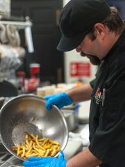 """The Deli kitchen manager James """"Mugsy"""" Mugford prepares loaded french fries for an order."""