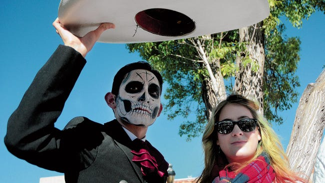 Daniel Duran uses his sombero to shield himself and Alex Peacher from the sun while taking in the sights at  a previous Día de los Muertos celebration on the Mesilla Plaza. This year's celebrations will run from Oct. 30 to Nov. 2.