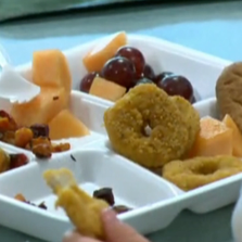 Student sits down and eats lunch in school cafeteria