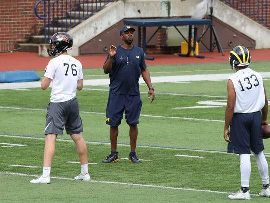 Pep Hamilton works with high school quarterback during the Michigan Football Elite Camp on June 23, 2017 at Michigan Stadium.