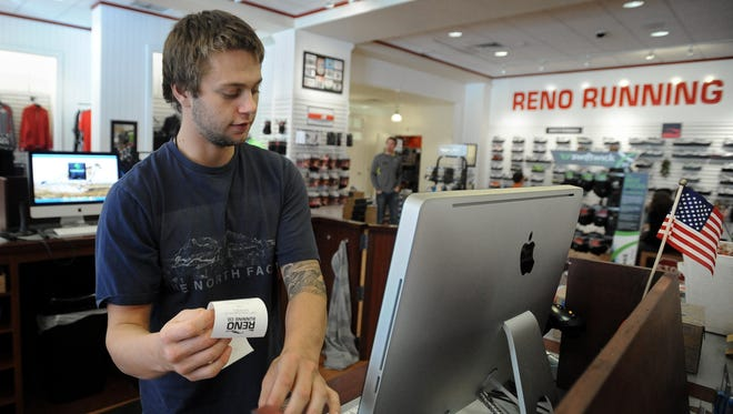 Reno Running Co. employee Sam Gaeta rings up a customer at the Summit Mall store in 2011.