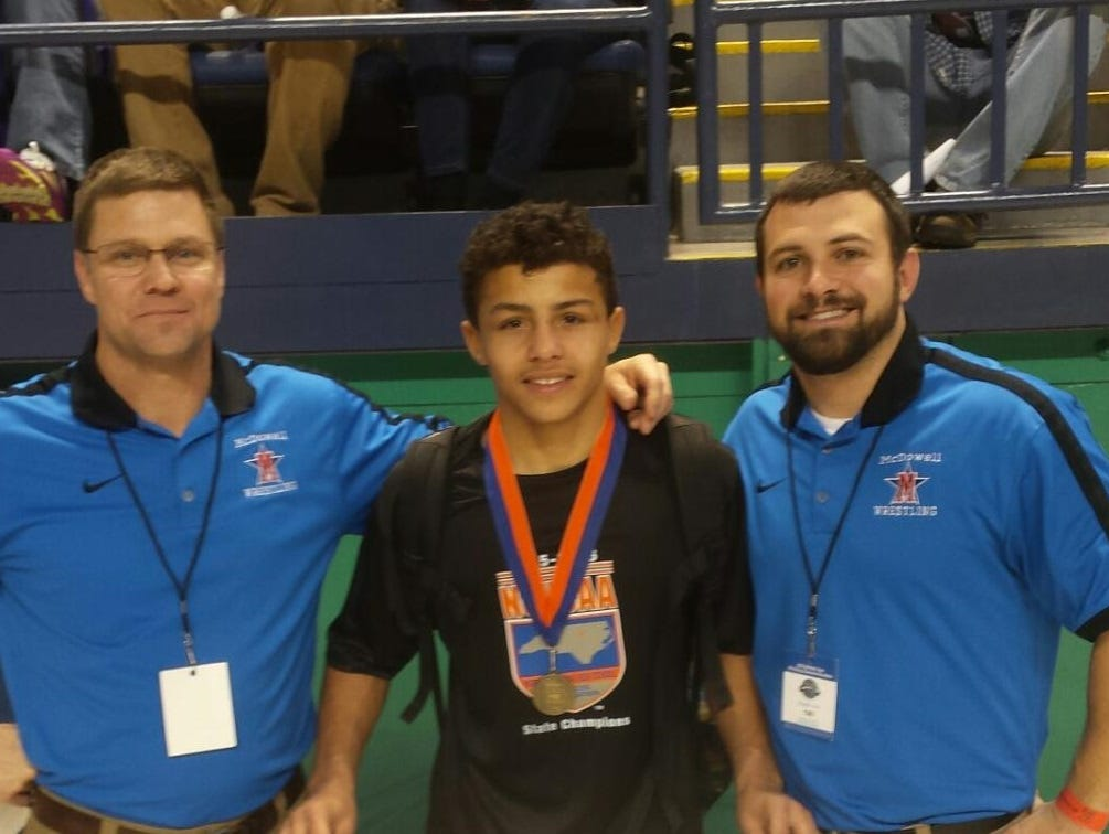 McDowell sophomore Toney McGee and his wrestling coaches.