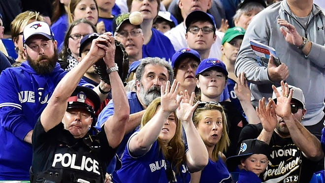 FILE - In this May 14, 2017, file photo, a police officer tries to catch a foul ball during seventh inning of a  baseball game between the Toronto Blue Jays and Seattle Mariners in Toronto. The Blue Jays announced Monday, Jan. 15, 2017, they will extend the protective netting at Rogers Centre to the outfield end of each dugout this season and increase the height of netting behind home plate by approximately 10 feet to 28 feet. (Frank Gunn/The Canadian Press via AP, File)