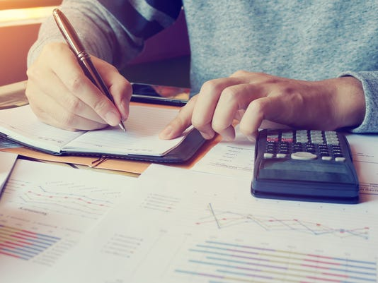 Young man doing finance in home with calculate about cost.