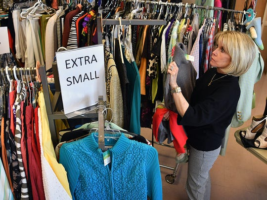 Carla Bolin hangs designer clothing in preparation
